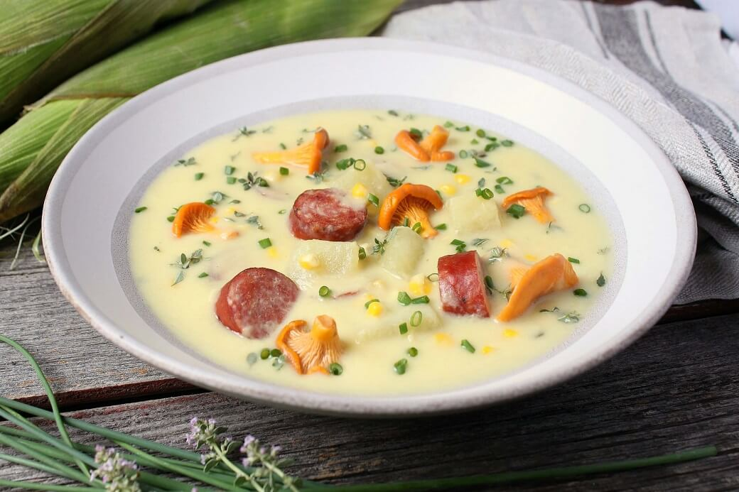 Hearty Farmer's Sausage Sweet Corn Chowder - A white bowl filled with creamy yellow soup with corn, sausage, potatoes and golden mushrooms garnished with fresh chives.