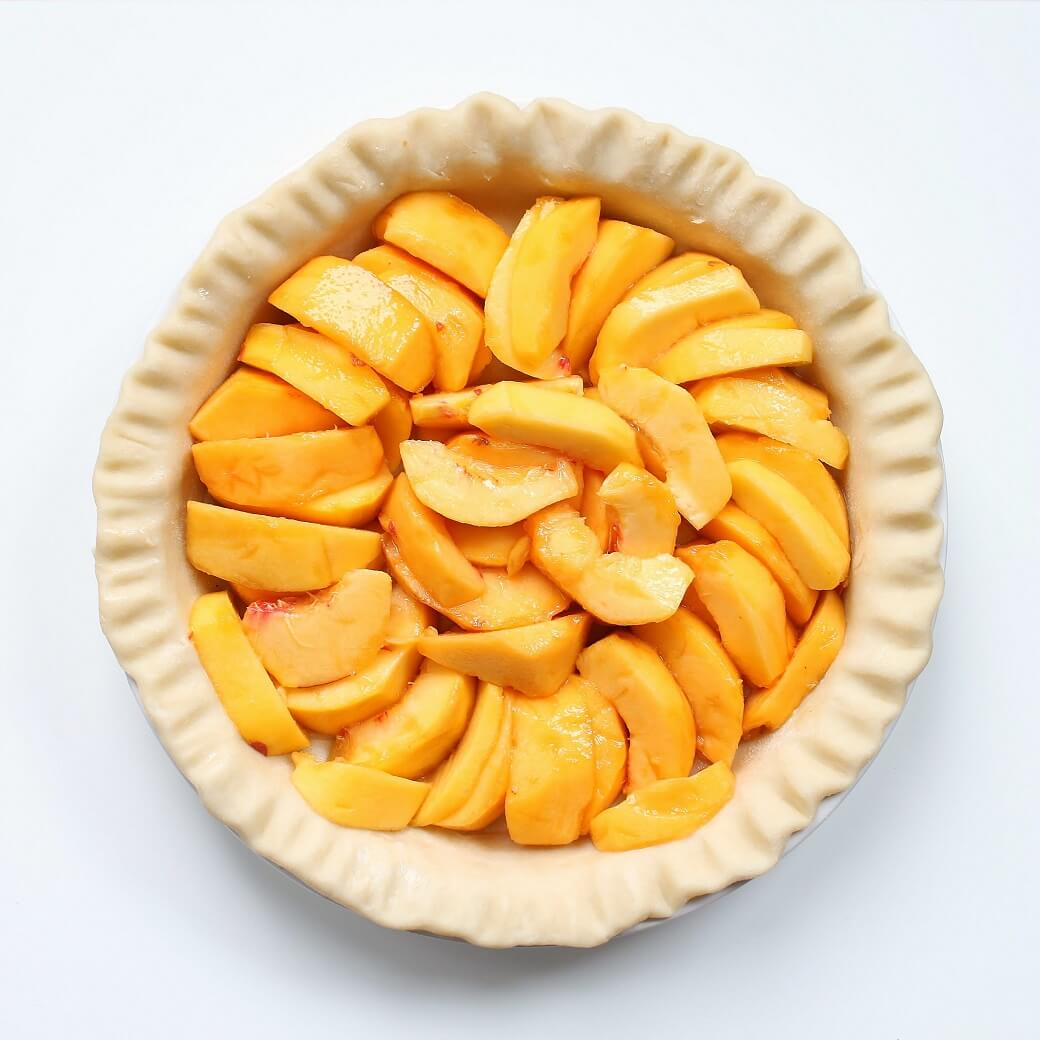 An unbaked pie shell filled with sliced fresh peaches.