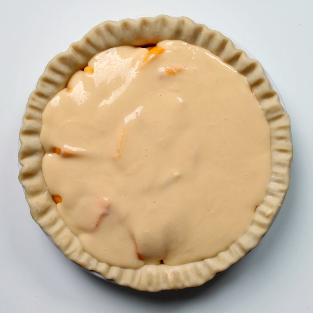 An unbaked pie shell filled with yellow custard and peaches.