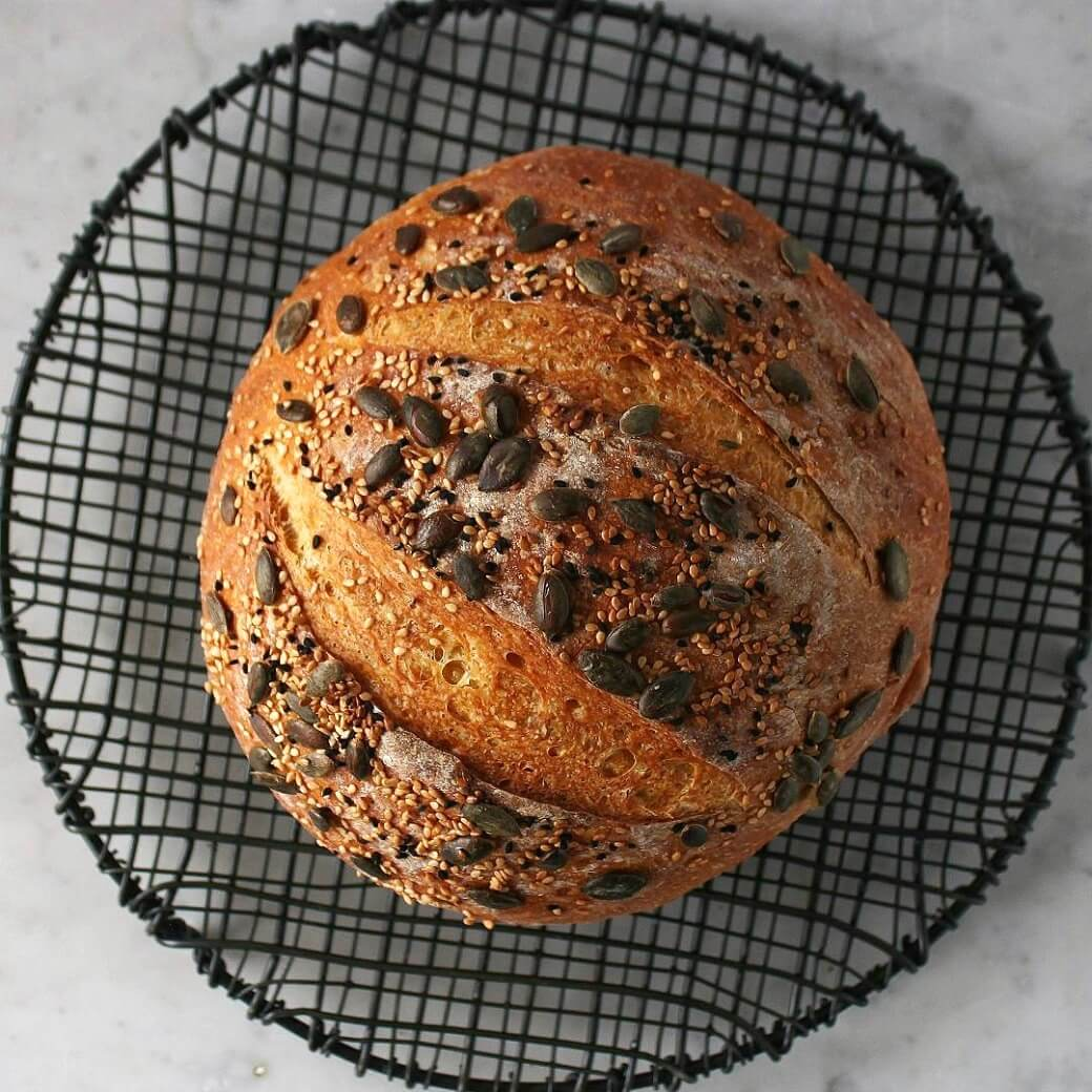 Pumpkin No Knead Bread -A boule of bread topped with pumpkin seeds on a black cooling rack.