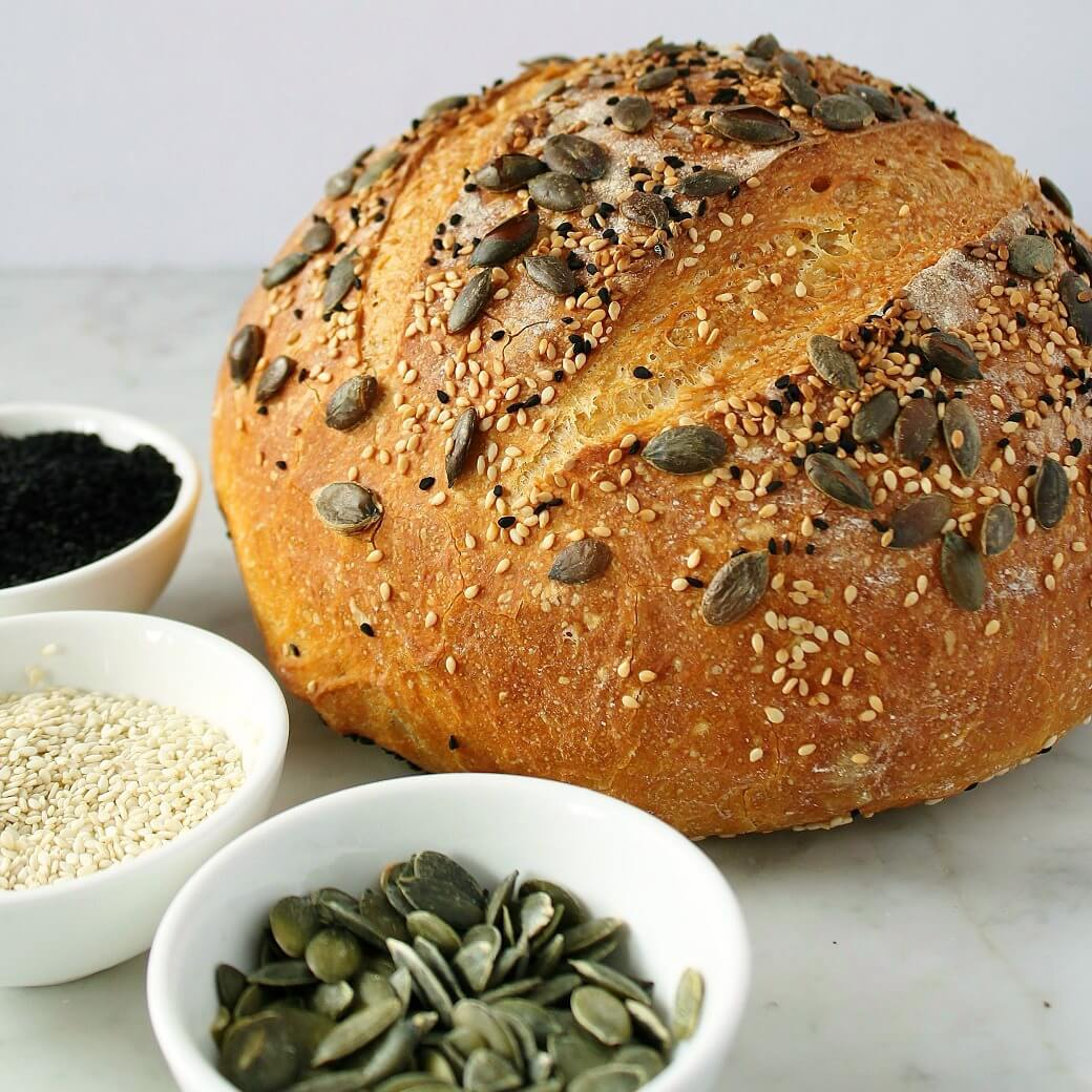 Pumpkin No Knead Bread - A round boule of bread topped with pumpkin seeds surrounded with small bowl of the same seeds.