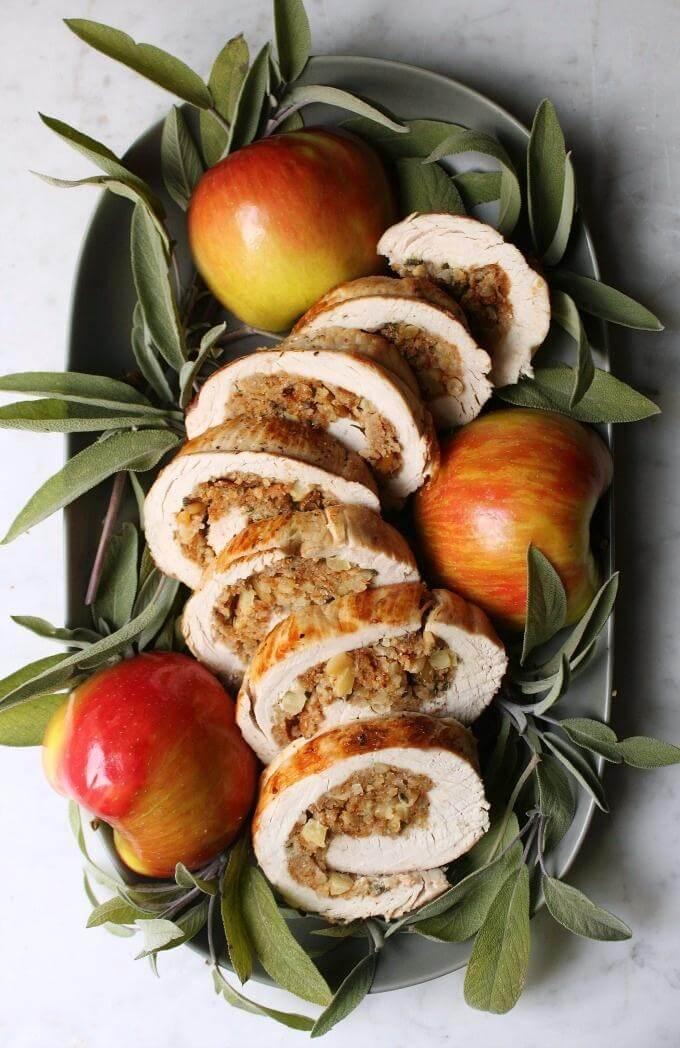 Apple Herb Stuffed Turkey Breast Recipe - Sliced stuffed Turkey breast on a platter surrounded by fresh sage and apples.
