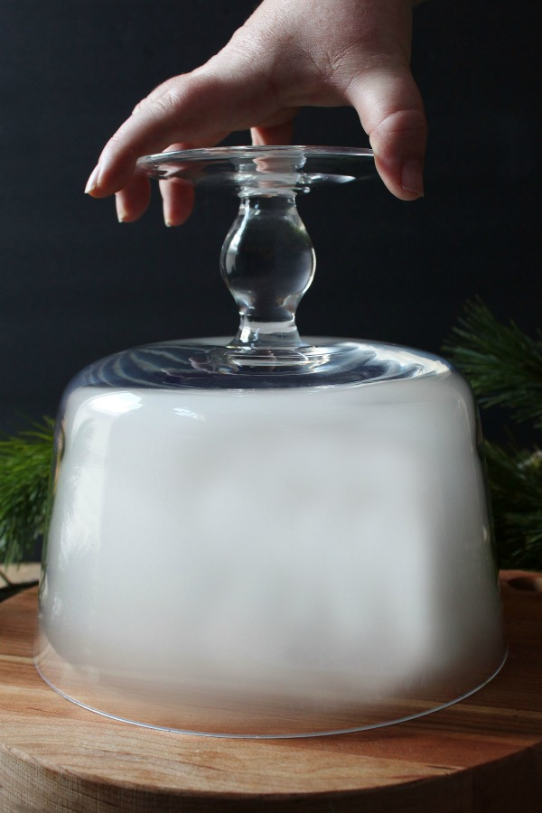 A hand reaches down to remove a glass cloche filled with white smoke.