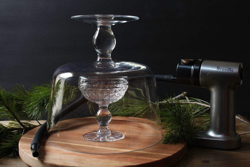 Cocktail smoking set up featuring a crystal coupe glass under a smoking cloche and a Breville smoking gun.
