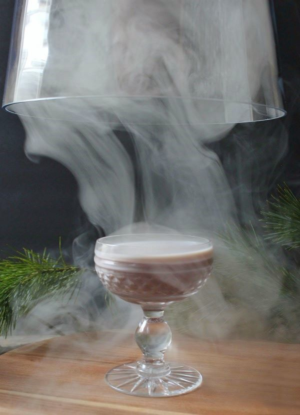 A glass cloche is removed to reveal a smoked mauve cocktail in a crystal coupe.