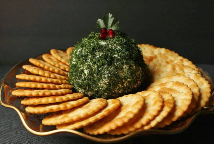 Dill Pickle Cheese ball - A cheese ball covered in fresh chopped dill sits in the middle of a circle of crackers.
