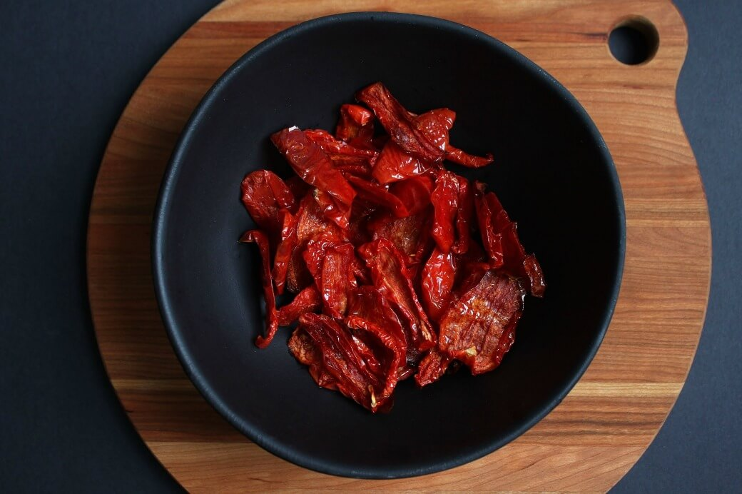 A black bowl filled with A black bowl of bright red dried tomatoes.