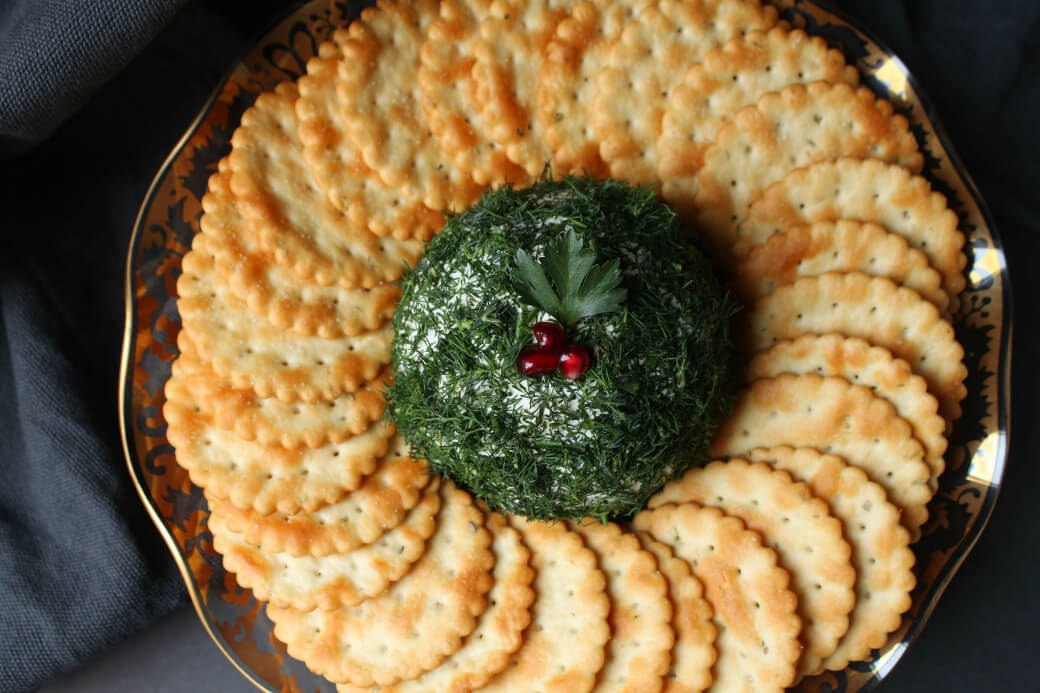 Dill Pickle Cheese ball - Top view of a cheese ball covered in fresh chopped dill sits in the middle of a circle of crackers.