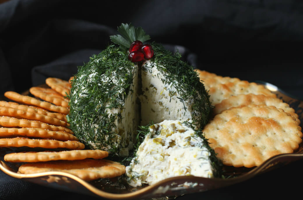 Dill Pickle Cheese ball - A cheese ball covered in fresh chopped dill with a slice missing sits in the middle of a circle of crackers.