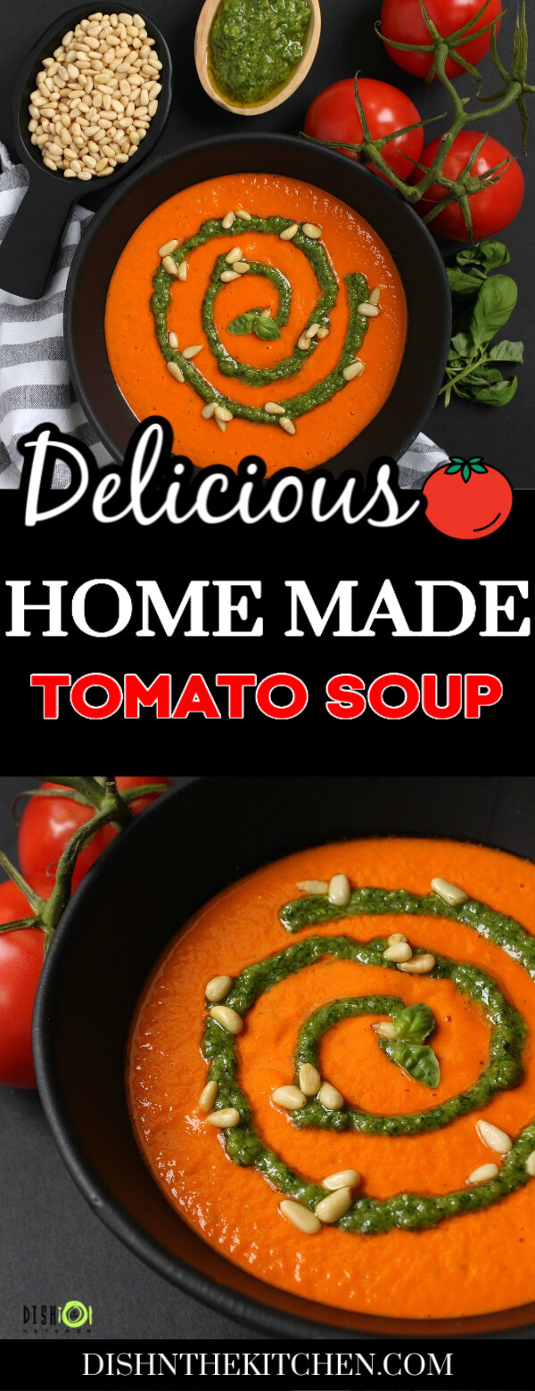 Pinterest image of a black bowl of bright orange tomato soup with a swirl of green pesto and pine nuts.