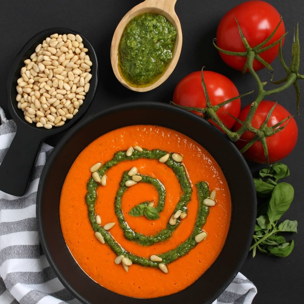A black bowl of bright orange creamy tomato soup with a swirl of green pesto and scattered pine nuts.