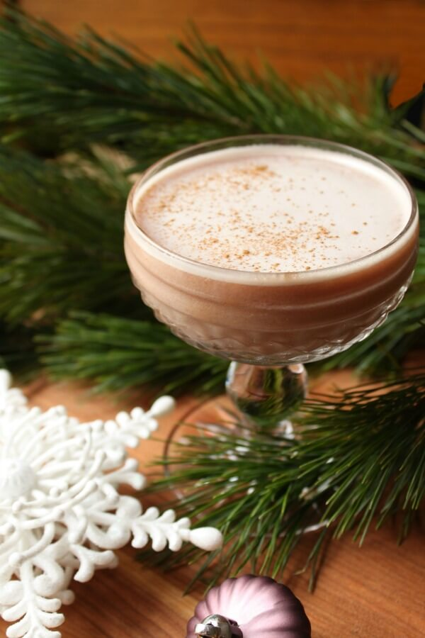 A mauve cocktail in a crystal coupe surrounded by fir branches and Christmas ornaments.