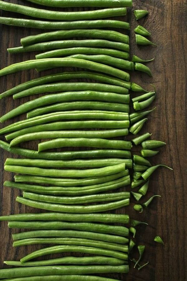 Overhead view of a tidy line of green beans with the tip cut off.