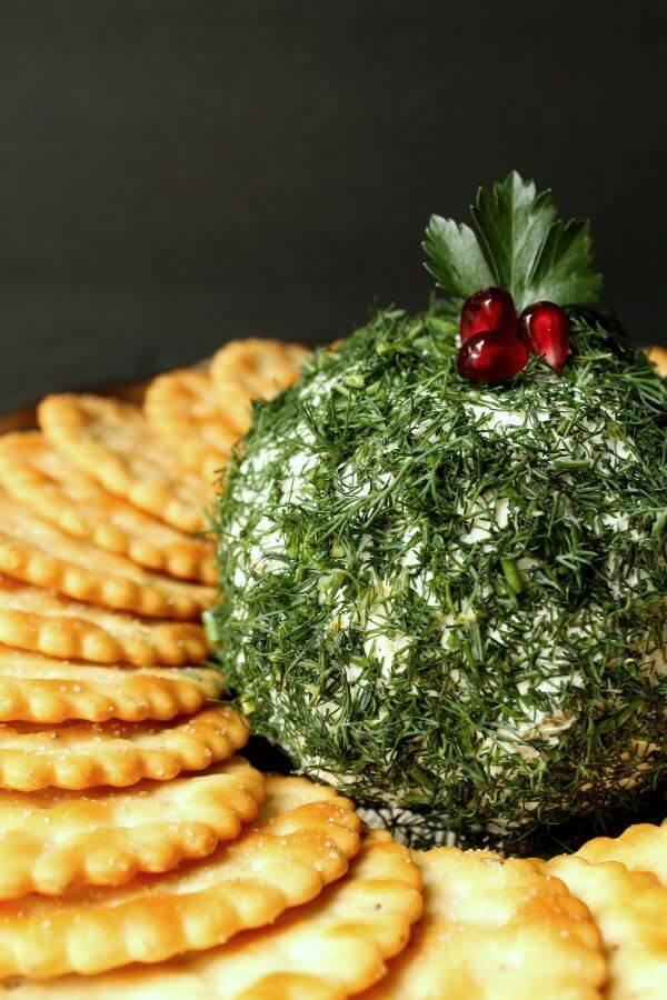 Dill Pickle Cheeseball - Side view of a cheese ball covered in fresh chopped dill sits in the middle of a circle of crackers.