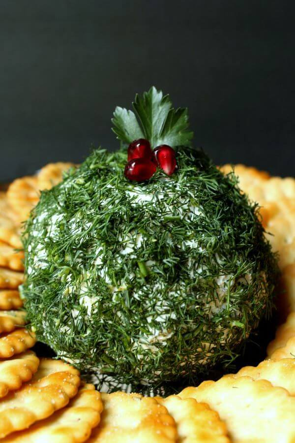 Dill Pickle Cheese Ball - Close up of a cheese ball covered in fresh chopped dill sits in the middle of a circle of crackers.