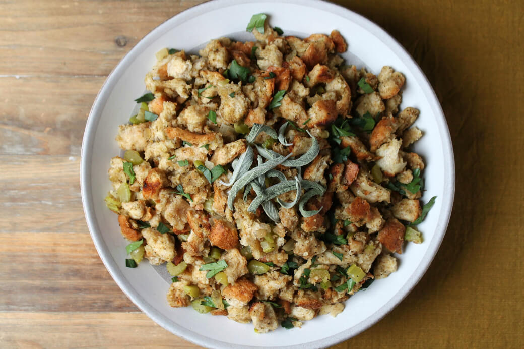 Homemade Stuffing Recipe featuring classic bread stuffing studded with onions and celery in a grey bowl.