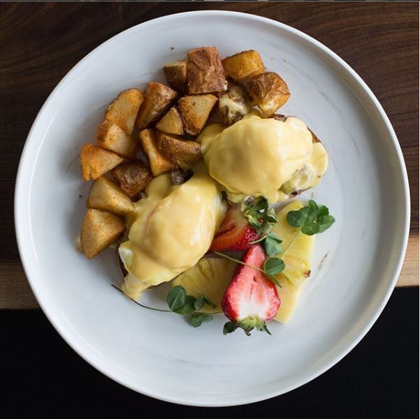 A plate of eggs Benedict and fried potatoes.