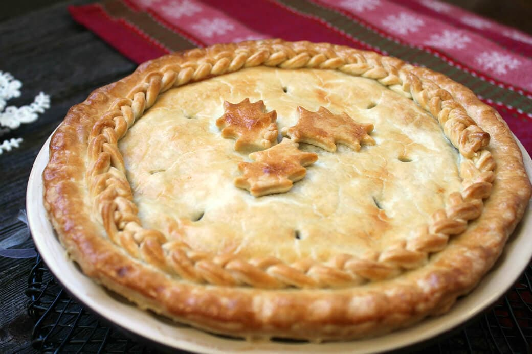 Christmas Eve Tourtière - A golden baked pie with braided pastry and holly design.