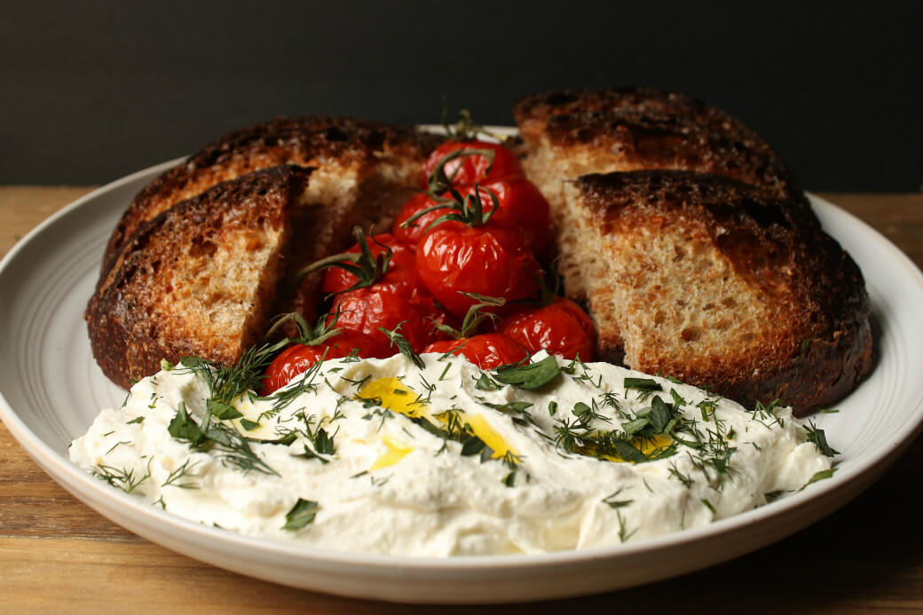 Whipped Feta - Roasted tomatoes and dark sliced bread surround a mound of creamy feta topped with olive oil and fresh green herbs.