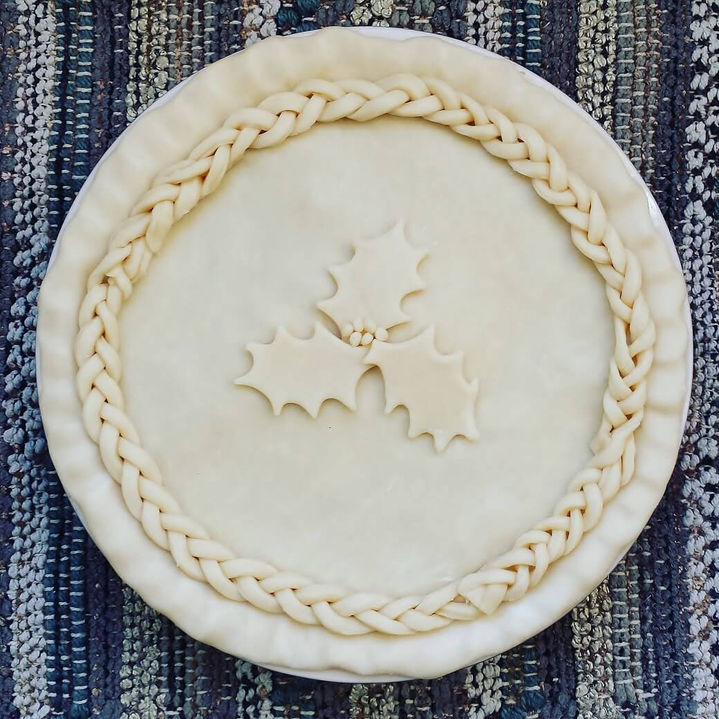 Christmas Eve Tourtière - Unbaked pie with braided pastry and holly design.