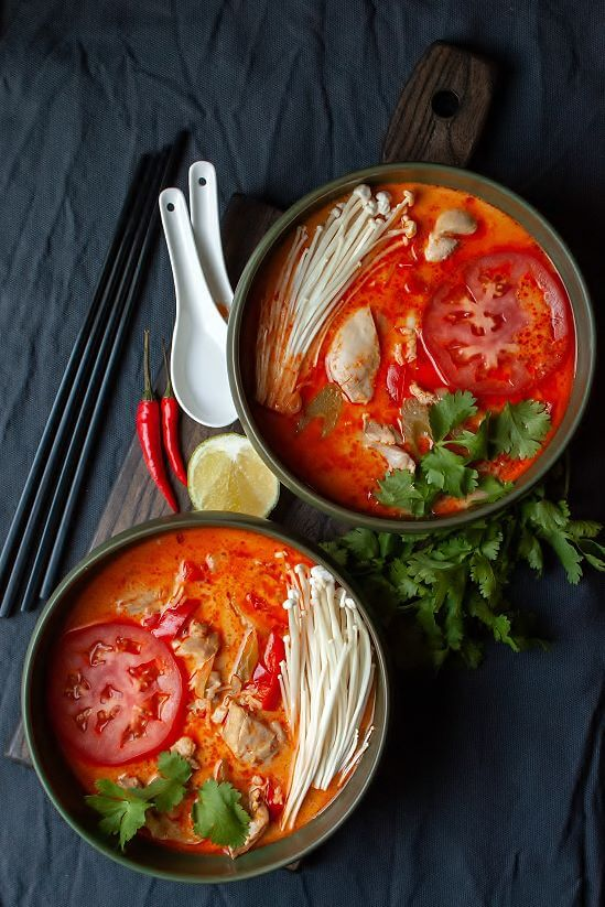 Thai Red Curry Chicken Soup - two green bowls of soup with creamy red broth, tomato, chicken, peppers, cilantro, and enoki mushrooms.