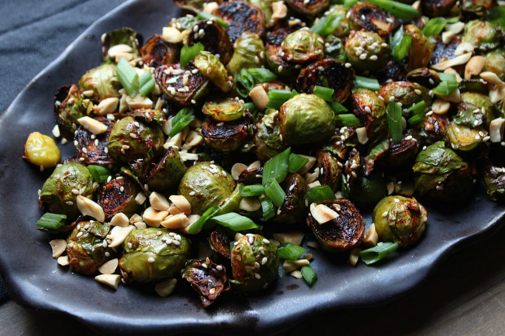 Maple Gochujang Roasted Brussels Sprouts - Dark roasted Brussels sprouts topped with sesame seeds, peanuts, and green onions on a black platter.