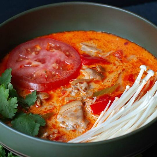 Thai Red Curry Chicken Soup - a green bowl of soup with creamy red broth, tomato, chicken, peppers, cilantro, and enoki mushrooms.