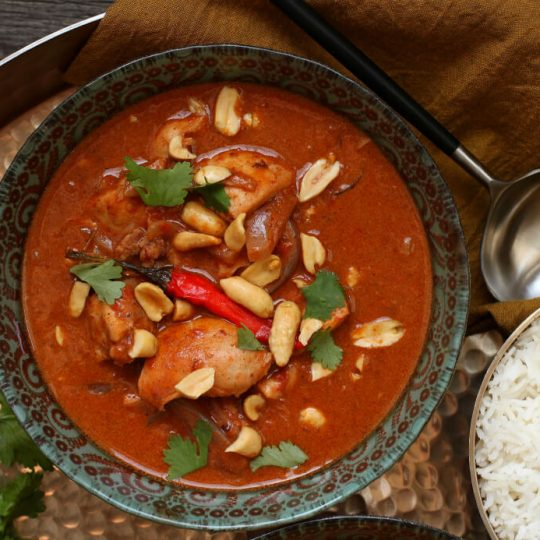 Peanut Butter Chicken Curry - One ornate bowl containing dark red curry with chicken, onions, red chili pepper, peanuts, and cilantro.