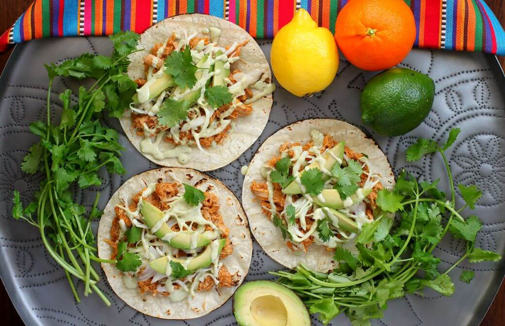 Citrus Pork Carnitas Tacos- Taco flat lay containing three tacos, a bright striped blanket, citrus fruit, avocado, and cilantro bunches.