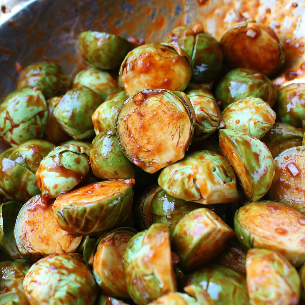Maple Gochujang Roasted Brussels Sprouts - Close up of gochujang and garlic coated Brussels Sprouts.