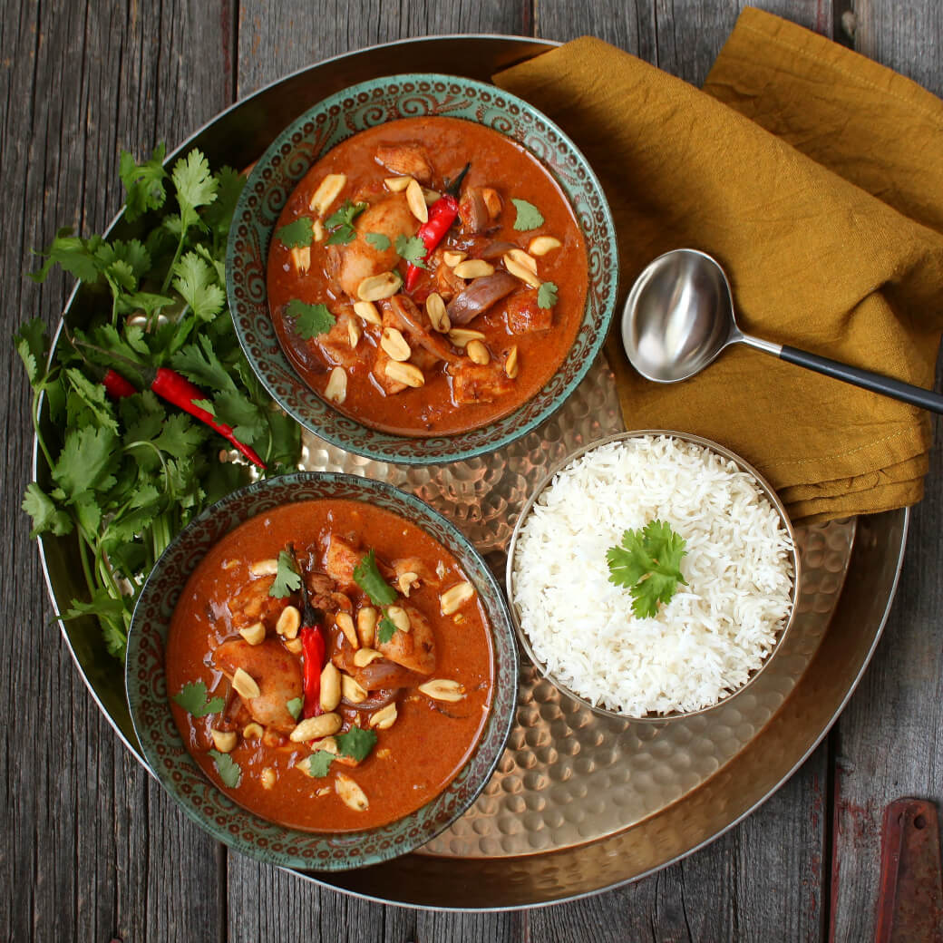 Peanut Butter Chicken Curry - Two ornate bowls containing dark red curry with chicken, onions, red chili pepper, peanuts, and cilantro.