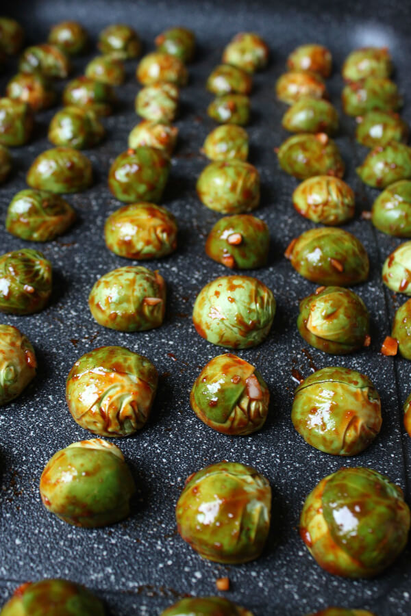 Maple Gochujang Roasted Brussels Sprouts - Gochujang coated Brussels Sprouts arranged on a baking tray.