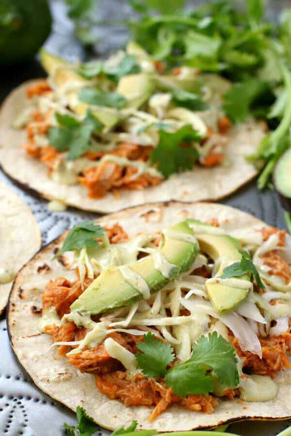 Citrus Pork Carnitas Tacos - two tacos topped with bright orange pulled pork, avocados, cilantro cream and cilantro.