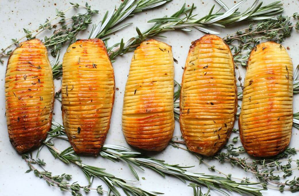 Crispy Herb Hasselback Potatoes - Five crispy golden potatoes rest on a bed of fresh herbs.