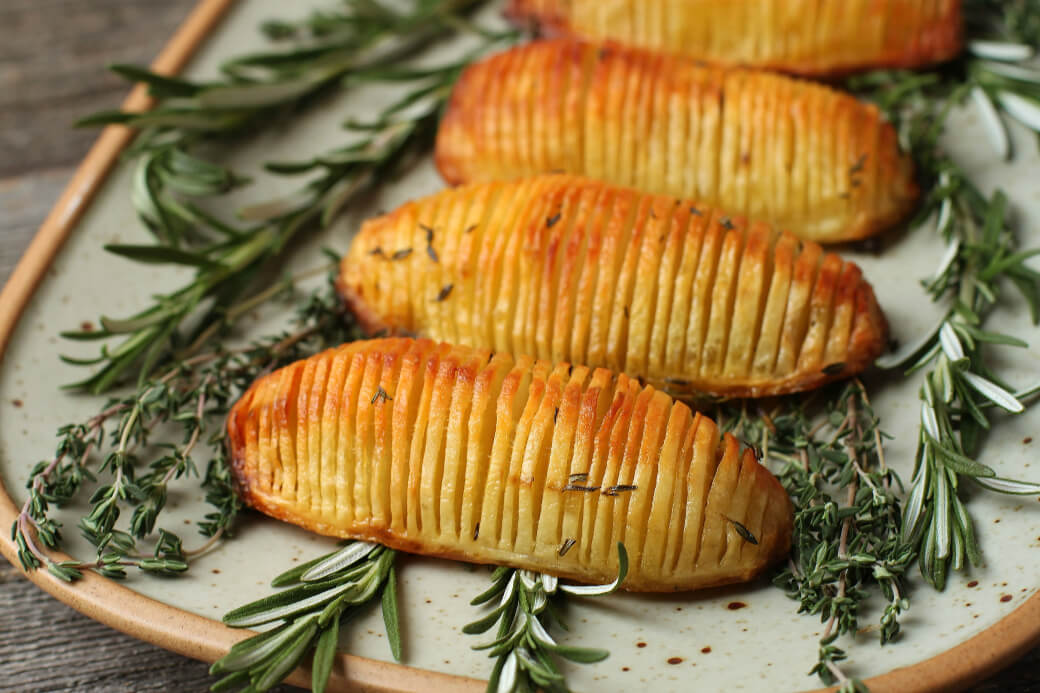 Crispy Herbed Hasselback Potatoes - Close up of crispy golden potatoes rest on a bed of fresh herbs.