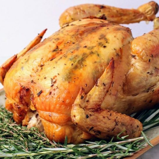 Dry Brine Chicken - A perfectly browned and roasted whole chicken sits on top of a bed of herbs.