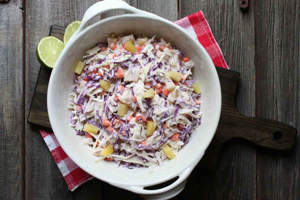 A multicoloured coleslaw with pineapple and lime in a white bowl.