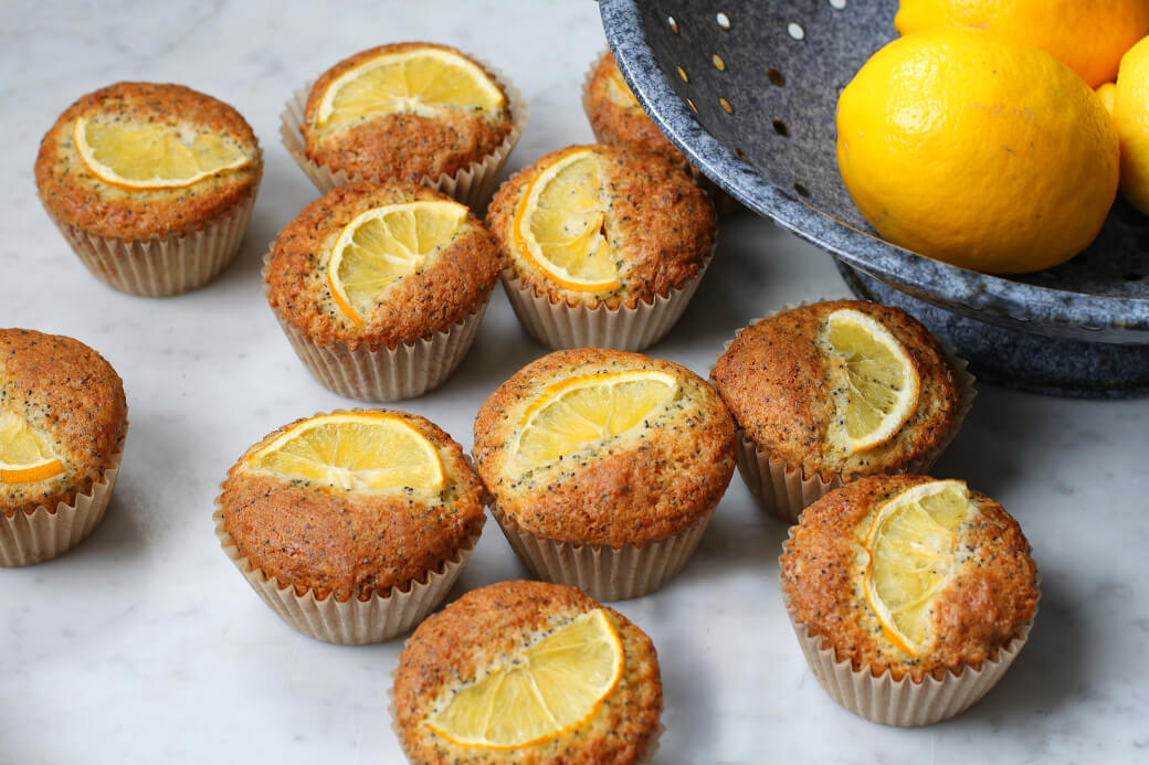 Bright yellow Meyer Lemons in a blue colander surrounded by muffins.