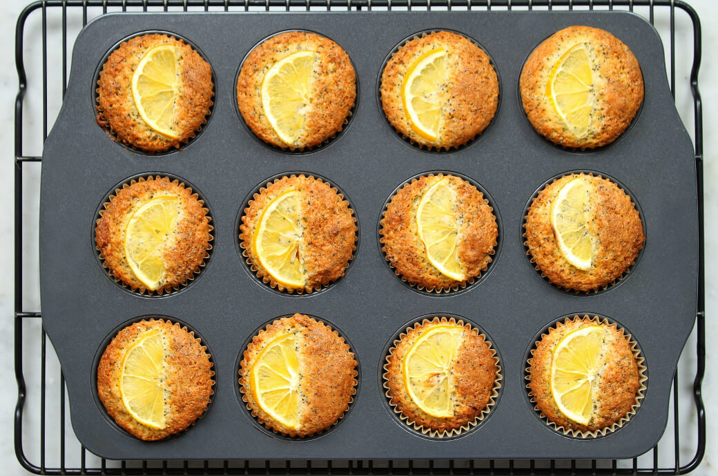 A muffin tin filled with a dozen Lemon Poppy Seed Muffins topped with lemon slices.