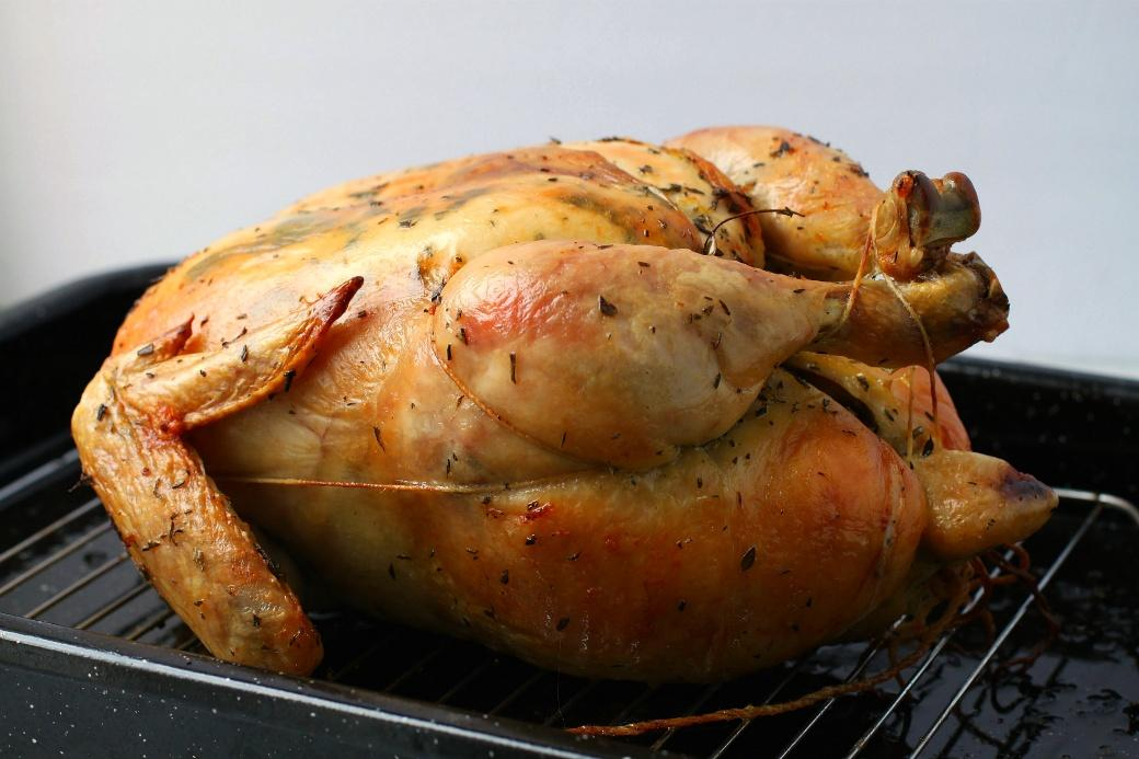 Dry Brine Chicken - A perfectly browned and roasted whole chicken sits inside a roasting pan.