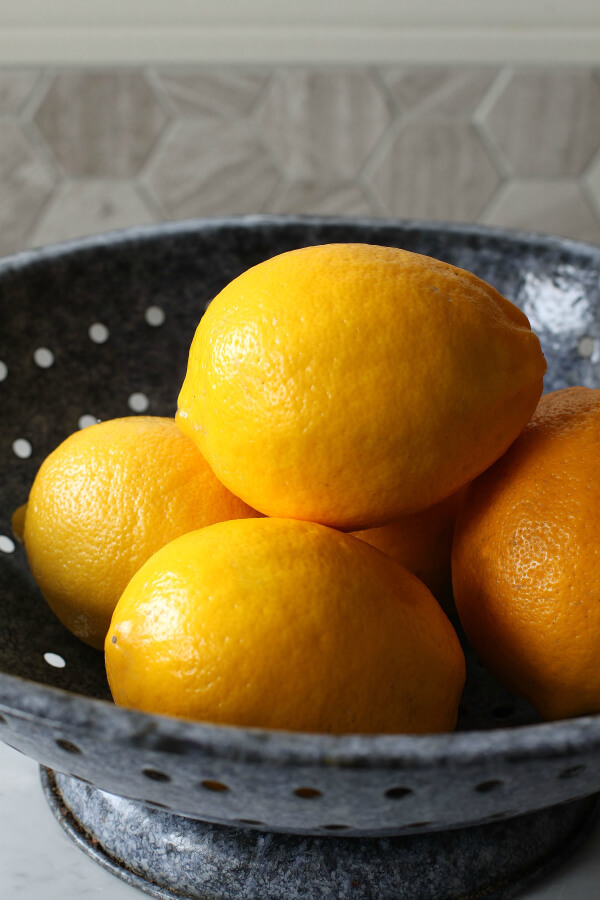 Bright yellow Meyer Lemons in a blue collander.