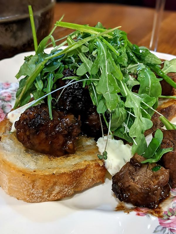 Rain Dog Bar - A slice of bread topped with chunks of short rib and arugula.