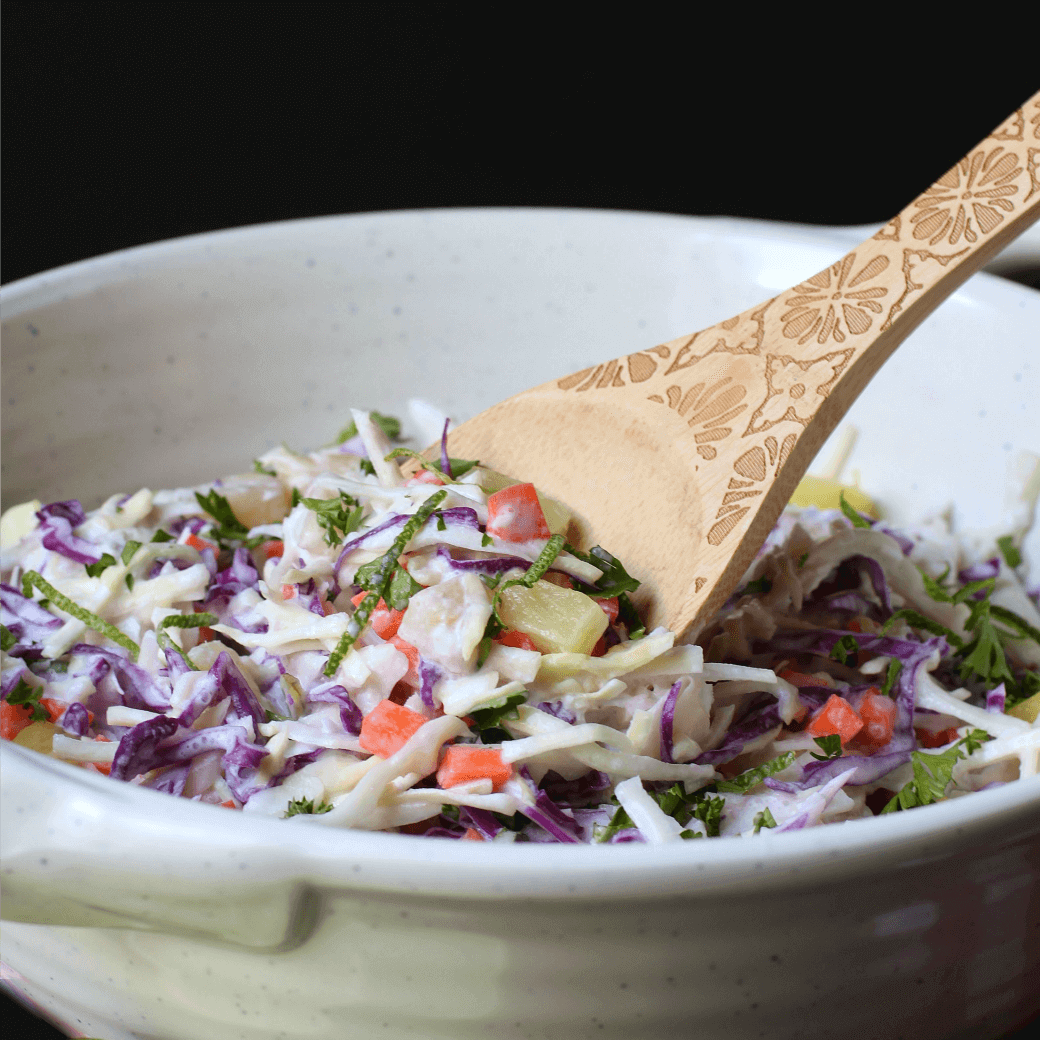 A multicoloured coleslaw with pineapple and lime in a white bowl with a wooden spoon.