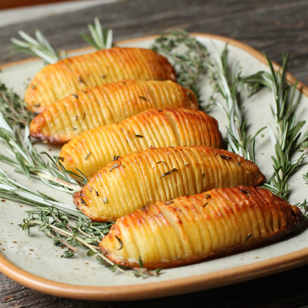 Crispy Herbed Hasselback Potatoes - Five crispy golden potatoes rest on a bed of fresh herbs.