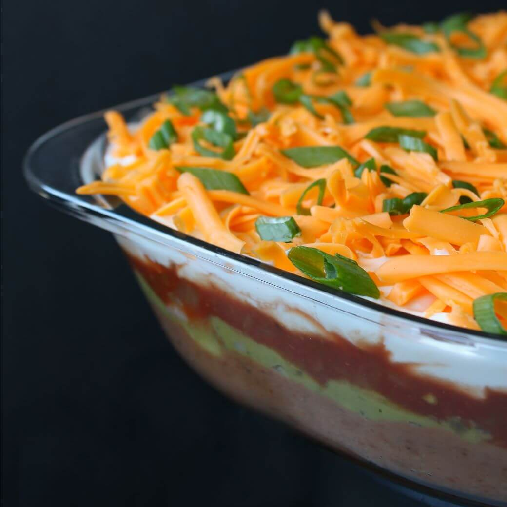 7 Layer Dip - A glass dish of layered dip topped with shredded cheese and sliced green onions.