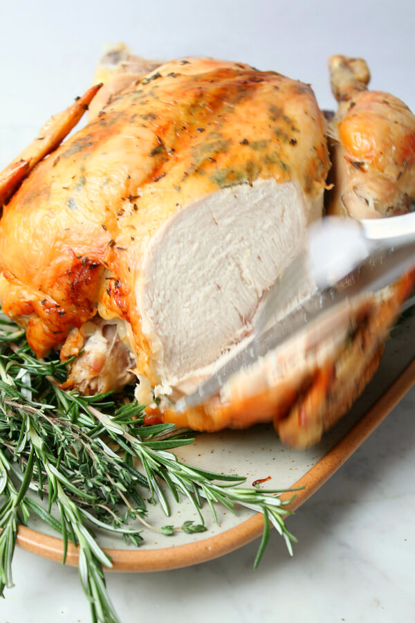Dry Brine Chicken - A perfectly browned and roasted chicken surrounded by herbs with a slice of breast meat removed.