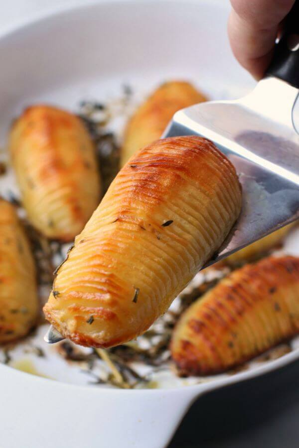 Crispy Herbed Hasselback Potatoes - Close up of crispy golden potatoes in a white baking dish.