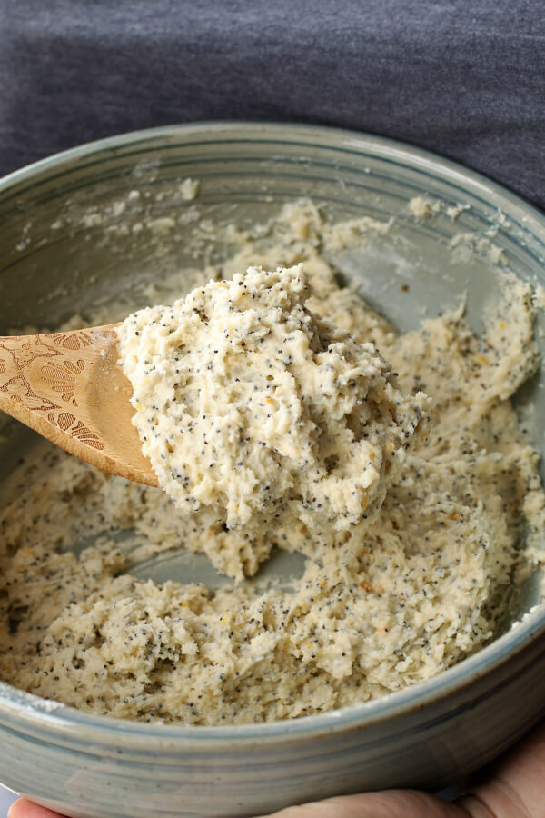 Raw muffin batter in a blue bowl with a wooden spoon.