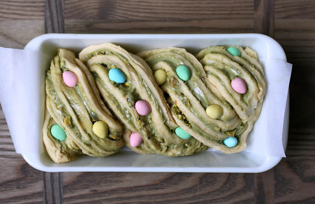 Pistachio Cream and Mini Egg Babka - Unbaked layers of swirled rich dough and pistachio cream dotted with mini eggs in a loaf pan.