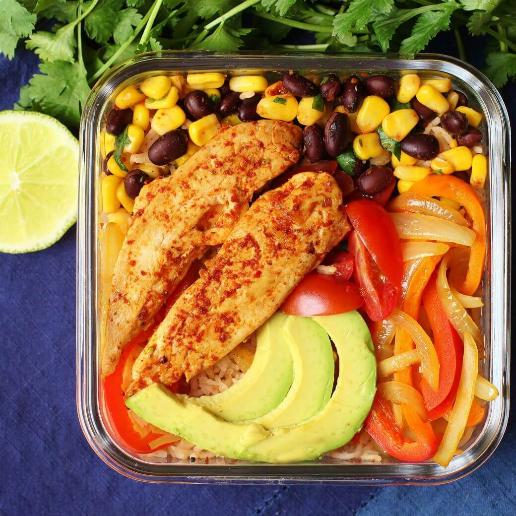 Simply Delicious Chicken Burrito Bowl - overhead shot of a square glass fridge container filled with chicken, rice, peppers, avocado, corn and beans.